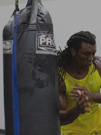 Football player training by hitting a punching bag
