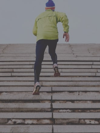 Man in yellow jacket exercising by running up stairs